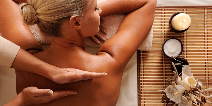 Close up image of a blonde woman receiving a back massage