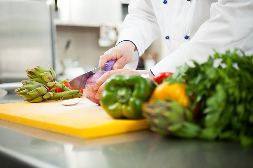 Close up image of a man preparing vegetables in a professional kitchen
