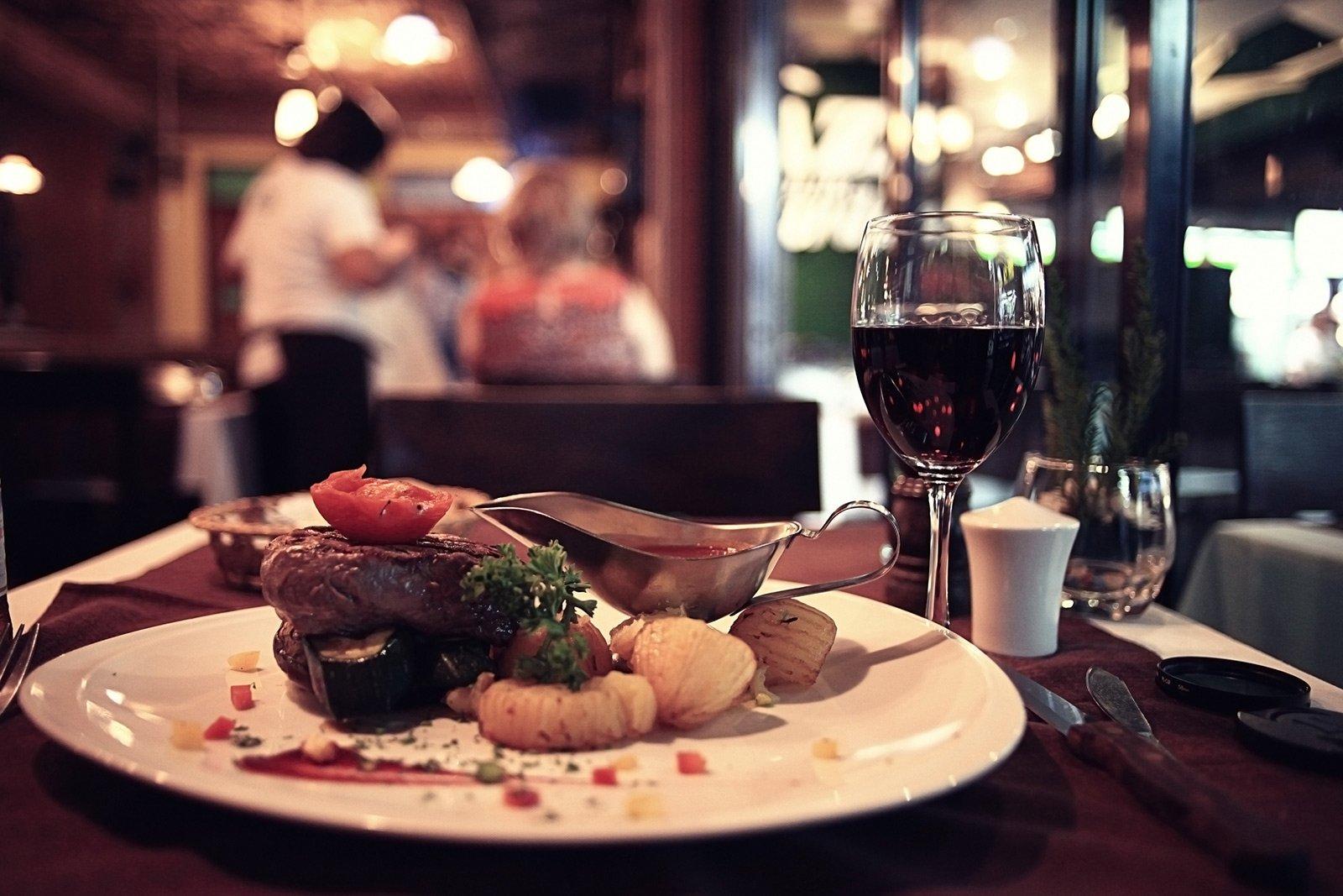 piatto di carne con bicchiere di vino rosso