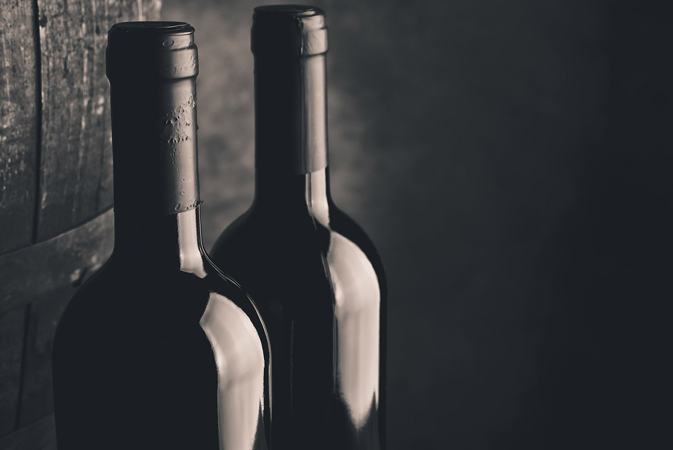 bottiglie di vino su sfondo nero e barile